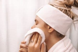 girl drying her face with a towel