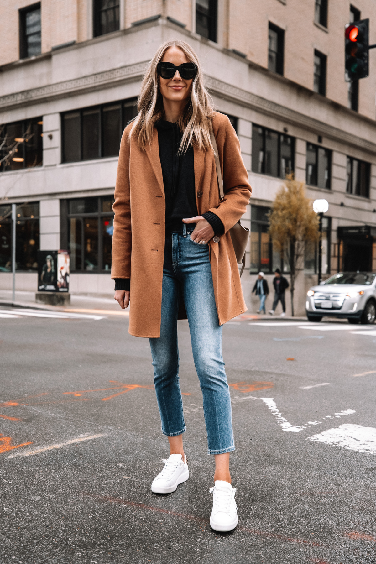 blue jeans with camel coat and white sneakers